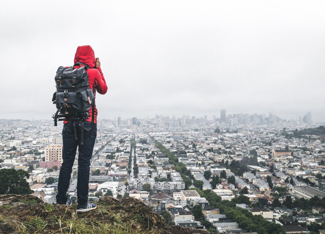 person standing on cliff over city