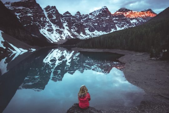 woman sitting on rock in front calm body of water and mountains view